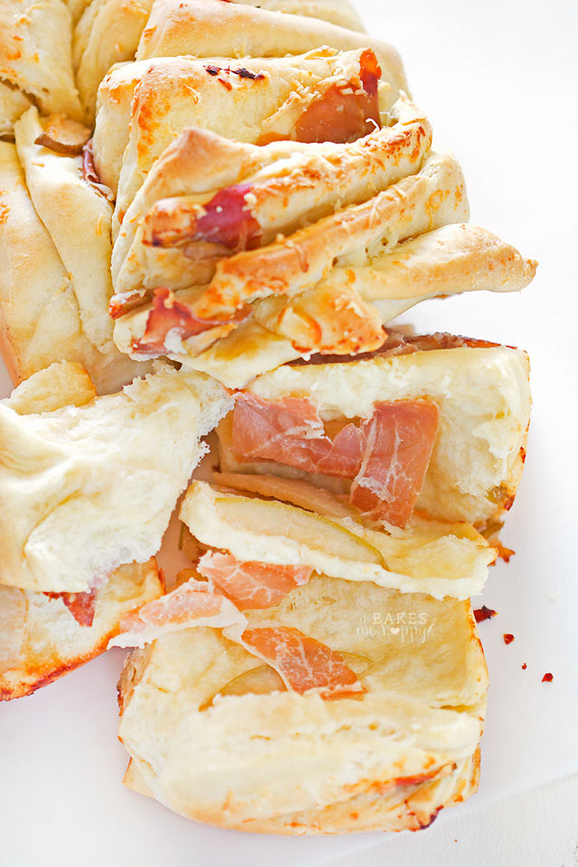 Rich, buttery bread is layered with delicious cheddar cheese, Prosciutto and thinly sliced pears in this Cheddar Pear Prosciutto Pull-Apart Bread.